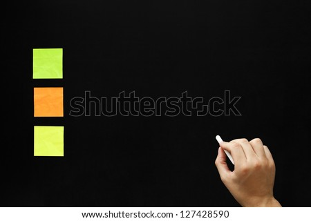 Hand writing something on blank blackboard with three different color sticky notes. - stock photo