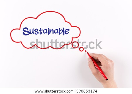 Hand writing Sustainable on white paper, view from above - stock photo