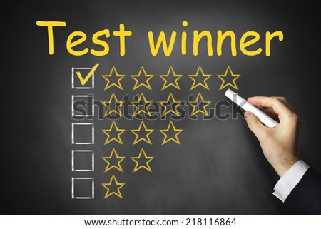 hand writing test winner on black chalkboard