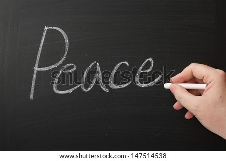Hand writing the word Peace on a used blackboard.