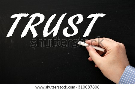 Hand writing the word Trust in white text on a blackboard with a stick of chalk - stock photo
