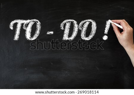 Hand writing to do list with chalk on black board - stock photo