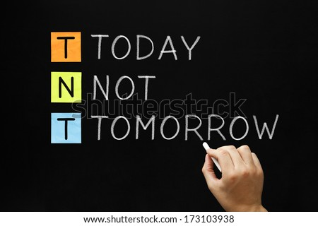 Hand writing Today Not Tomorrow with white chalk on blackboard. - stock photo