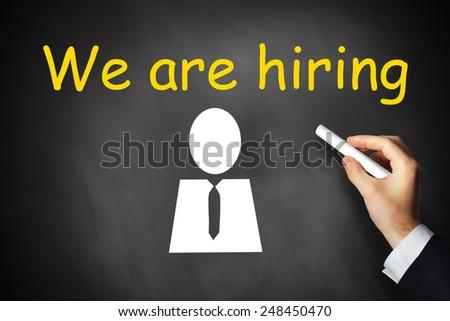 hand writing we are hiring on black chalkboard employee symbol - stock photo