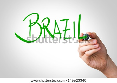 Hand writing with a green mark on a transparent board - Brazil - stock photo