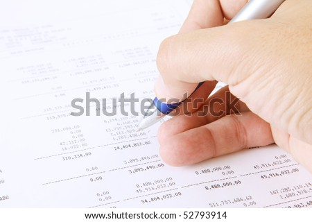 Hand writing with a pen reviewing the numbers