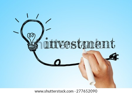hand writing word of  investment with lightbulb background
