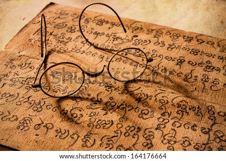 Hand Written Ancient Treatise of Lanna character with very old glasses - stock photo