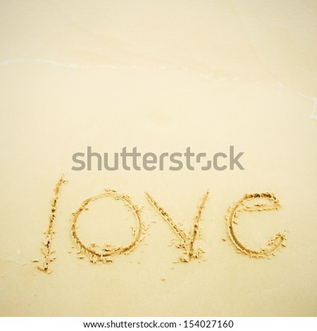 Hand written love on sand and beach - stock photo
