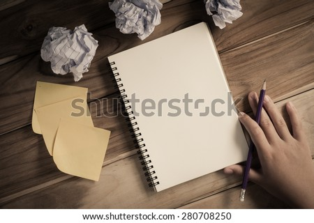 Hand-written note in pencil on a wooden table - hand focus - stock photo