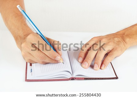 Hand written notes in pencil in a notebook on a white background - stock photo