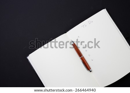 Hand written to do list on notepad with wooden stylus pen