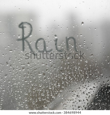 Hand written word Rain on a window glass with droplets - stock photo
