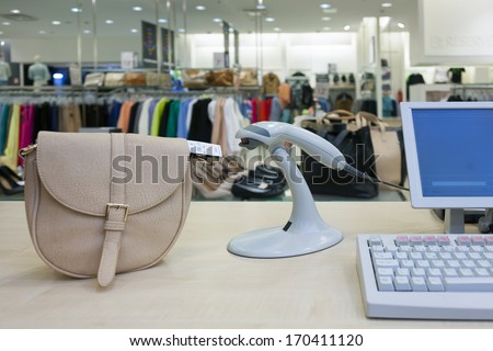 Handbad in fashion clothing store. Cashier register, scanner computer on sales counter in shop. - stock photo
