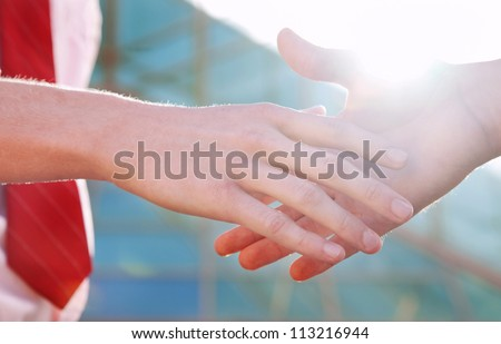 handclasp of two persons near the office - stock photo