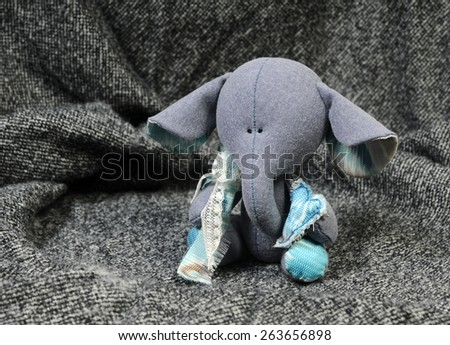 handcrafted beautiful sad baby elephant interior toy holding a blue heart made of all natural materials on grey woolen background - stock photo