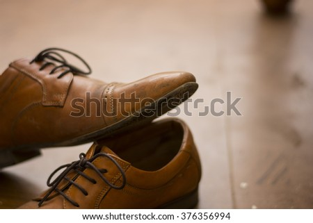 Handcrafted Brown Leather Shoes kept on Floor on a Sunny Day with a Nice Bokeh - stock photo