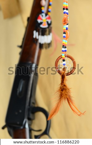 Handcrafted Native American Cream Catcher with western rifle and Thunderbird symbol against buckskin background. - stock photo