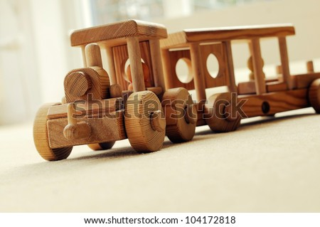 Handcrafted wooden train on an beige carpet, retro toned image. - stock photo