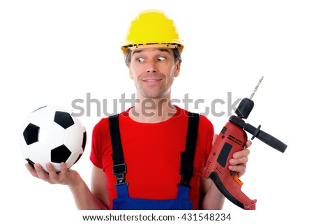 handcrafter with helmet and drilling machine and soccer ball - stock photo