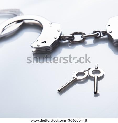 Handcuff, close up on keys - stock photo