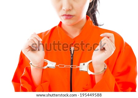 Handcuffed Asian young woman in prisoners uniform - stock photo