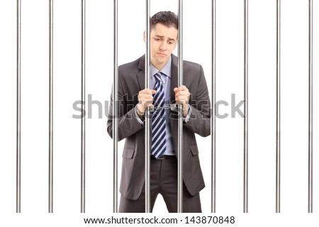 Handcuffed businessman in suit posing in jail and holding bars, isolated on white background - stock photo