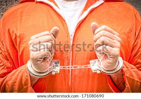 Handcuffed Hands - Guantanamo prison orange clothes - stock photo