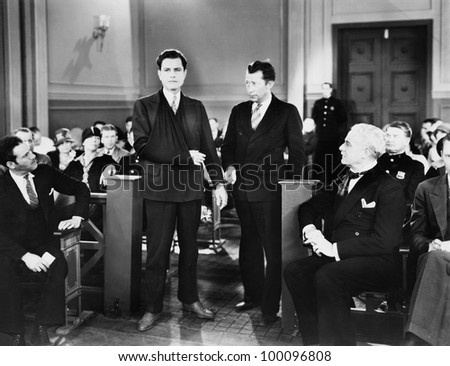 Handcuffed injured man in crowded courtroom - stock photo