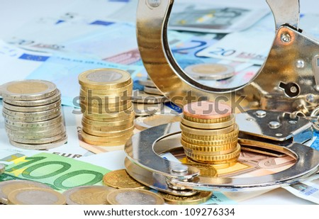 handcuffs and euro money - stock photo