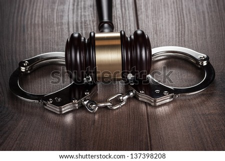 handcuffs and judge gavel on brown wooden table background - stock photo