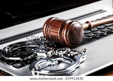 handcuffs and judge gavel on computer cyber crime concept  - stock photo