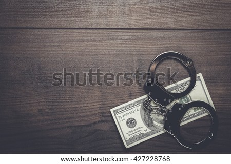 handcuffs and one hundred dollars on wooden table