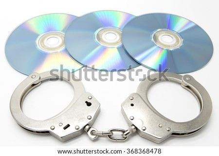 Handcuffs and optical discs - Software piracy concept - stock photo