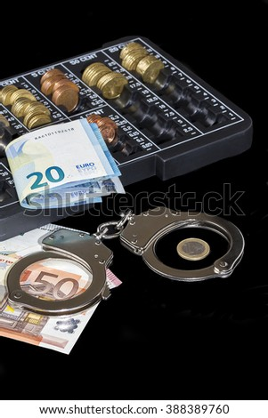 handcuffs, euro bills and a organizer of euro coins on black background