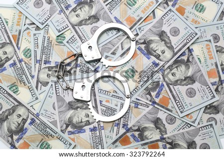 handcuffs on a pile of dollars - stock photo