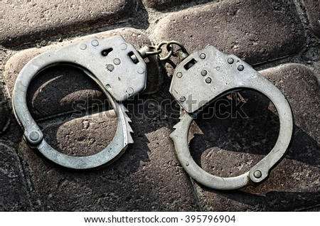 Handcuffs on a stone floor taken closeup.Toned image. - stock photo