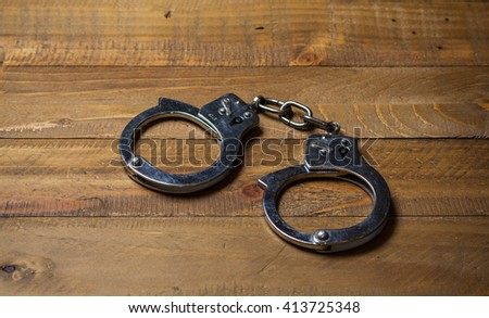 Handcuffs on a wooden table - stock photo