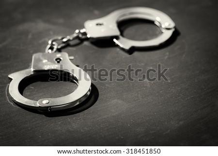 Handcuffs on black background - stock photo