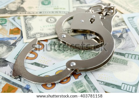 Handcuffs on dollar banknotes, close up. Corruption concept - stock photo