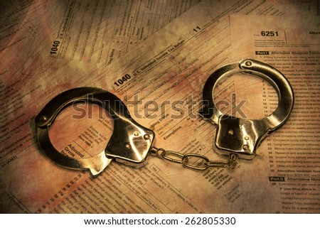 Handcuffs on form 1040 - federal tax fraud and scam - stock photo