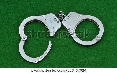 Handcuffs on green background - stock photo