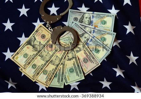 handcuffs on money background and american flag - stock photo