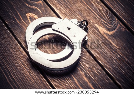 Handcuffs on paper background - stock photo