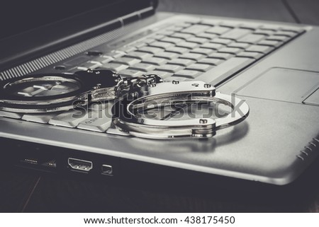 handcuffs on the laptop cyber crime concept - stock photo