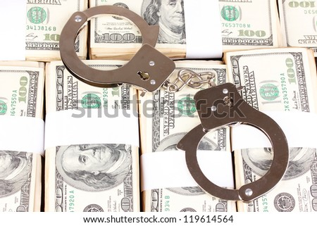 Handcuffs on the packs of dollars close-up