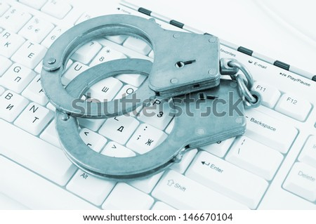 Handcuffs on white computer keyboard  - stock photo