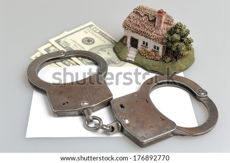 Handcuffs, toy house and white envelope with money on gray background - stock photo