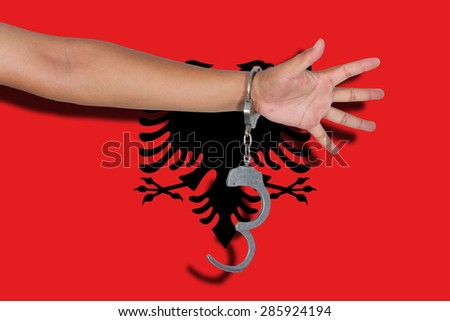 handcuffs with hand on Albania flag