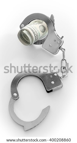 Handcuffs with rolled dollar banknotes, isolated on white. Corruption concept - stock photo